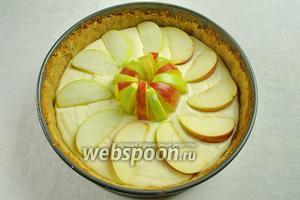 Аккуратно разложить яблоки по диаметру и в центре десерта. Поставить чизкейк в духовку, нагретую до 180 °С , выпекать в течение 50 минут. Сначала чизкейк накройте пергаментной бумагой. За 15 минут до окончания выпечки, бумагу снять.