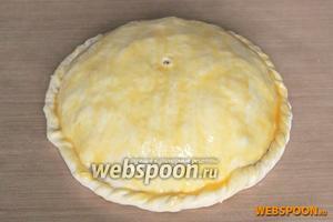 Края курника скрепите и подверните, затем обмажьте всё тесто сырым яичным желтком.