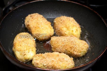 Обжаривать картофельные зразы нужно на сковороде. Разогреть в сковороде 3-4 столовые ложки растительного масла. Взбить вилкой 1 яйцо и подготовить панировочные сухари. Кстати панировочные сухари готовьте по нашему рецепту, они намного вкуснее магазинных. Обмакнуть в яйцо, затем в сухари и обжарить на среднем огне с двух сторон до румяного цвета  около 1 минуты.