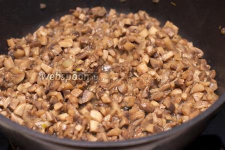 Разогреть 2 столовые ложки растительного масла и обжарить грибы с луком до румяного цвета 15-20 минут на среднем огне.