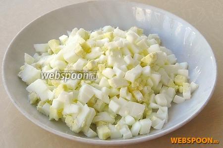 Яйца залить водой, довести до кипения и варить в течение 10 минут, а затем остудить в холодной воде, очистить и нарезать мелкими кубиками.