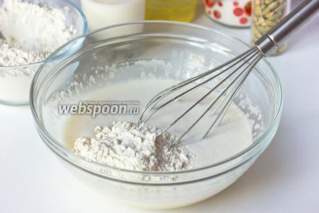 Вливаем половину молока и всыпаем муку, смешанную с содой. Вымешиваем тесто.