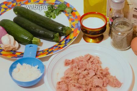 Для приготовления блюда вам понядобятся цукини, консервированный тунец, кедровые орешки, сыр Пармезан, панировочные сухари, яйцо, оливковое масло, соль, перец, лук, чеснок и орегано.