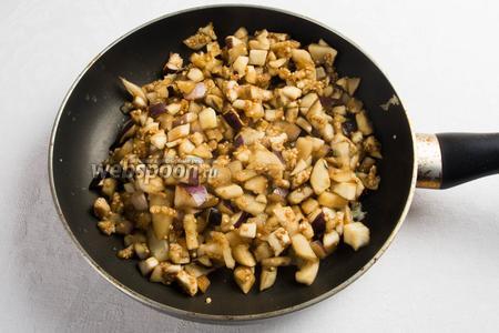 Баклажаны промыть под холодной проточной водой и отжать. Выложить на сковороду к чесноку. Жарить в течение 10-15 минут до готовности баклажан.