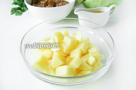 Картофель чистим и нарезаем кубиками, промываем. В кастрюлю наливаем воду, бросаем в неё картофель, ставим на большой огонь, даём воде закипеть, убавляем огонь до минимума и варим, накрыв крышкой.