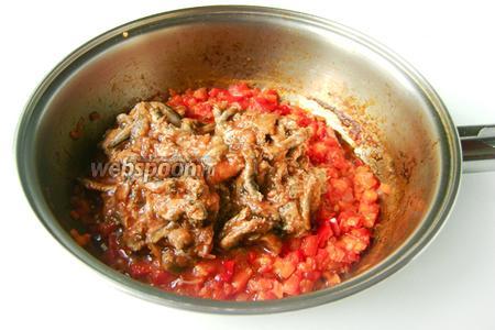 Добавляем в обжарку кильку вместе с консервным томатным соусом. Тушим на медленном огне около 5 минут.