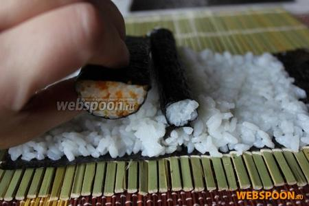 На половину листа нори уложите тонкий слой риса с отступом от одного края примерно 1,5 см. Посередине поперёк выложите треугольной горочкой рис и укройте её куском листа нори примерно 8х2 см — это усики.