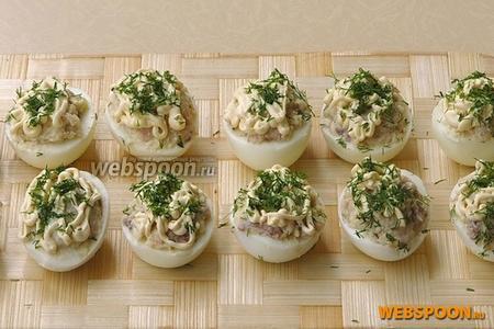 Посыпать фаршированные яйца рубленой зеленью укропа.