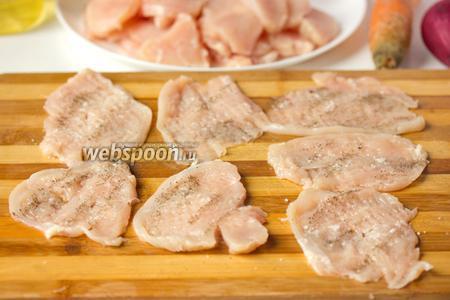 Слегка отбиваем кусочки куриного филе, солим и перчим их.