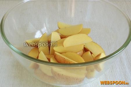 Не счищая кожуру разрезать каждую картофелину на 8 долек вдоль.