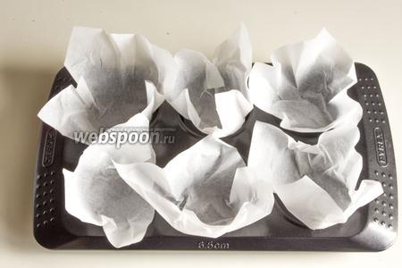 Порежьте бумажные квадратики, чтобы сделать конвертики для маффинов, и вложите их в формы.