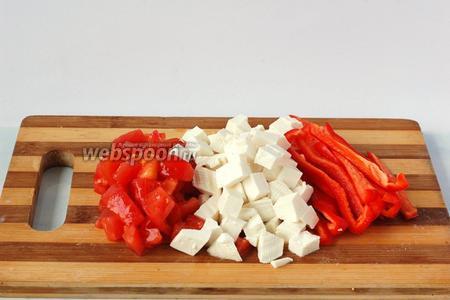 Помидор очистить от кожицы, а перец от семян. Нарезать брынзу и помидор кубиками, а перец — полосками.
