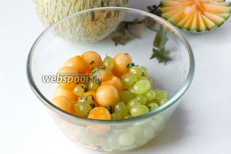 Заправляем дынные шарики и виноград сиропом, перемешиваем.