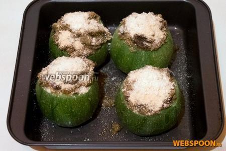 Выложите на смазанные противень цукини и фаршируйте их полученной смесью. Посыпьте сверху панировочными сухарями.