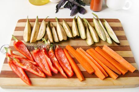 Овощи моем, морковь чистим, из перца вырезаем семена и внутренние перегородки. Нарезаем овощи брусками прямо с плодоножками (баклажанчики на четвертинки, перец на 8 частей и длинную морковь на 8 частей).