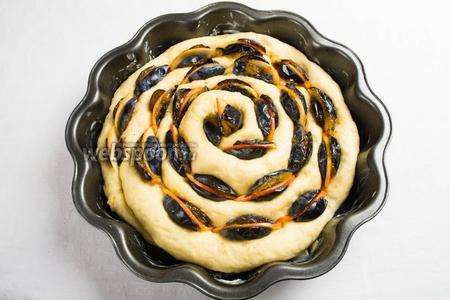 Перенести тесто в смазанную форму. Начинять и одновременно скручивать пирог кольцом (швом вниз). Дольки слив и яблок вложить между тестом по спирали. Поставить пирог на 15 минут в тепло.