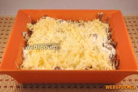 Распределить сметанную массу поверх, разровнять при помощи вилки. Посыпать оставшимся сыром.