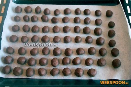 Из охлаждённого теста скатайте шарики размером с лесной орех и выложите на выстланный пергаментом поднос. Поставьте в холодильник на 30 минут.