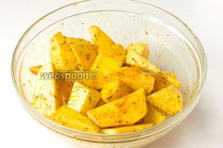 Тщательно перемешиваем руками, чтобы каждый кусочек картофеля был покрыт маслом и пряностями.