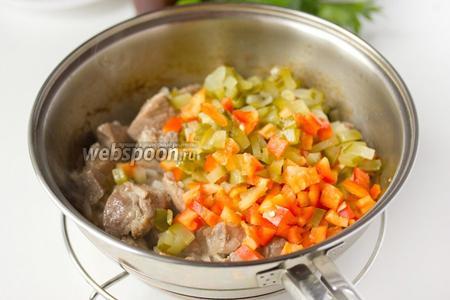 Добавляем в сковороду нарезанные солёные огурцы и сладкий перец. Обжариваем около пяти минут на сильном огне.