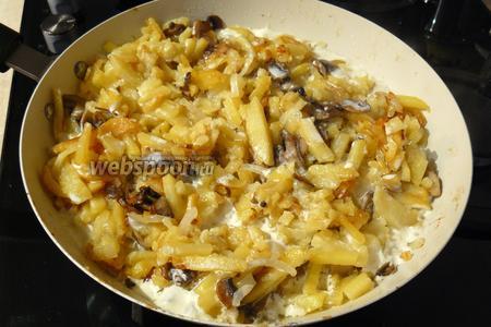 Ещё через 3 минуты залейте картофель сливками и жарьте под крышкой 5 минут, периодически помешивая.