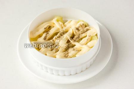 Ставим на плоскую тарелку формовочное кольцо, выкладываем первый слой из картофеля, поливаем его майонезом, слегка подсаливаем и перчим.