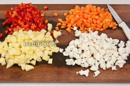 Морковь и картофель почистить и нарезать на мелкие кубики. Болгарский перец очистить от сердцевины и также нарезать, а цветную капусту разделить на мелкие соцветия.