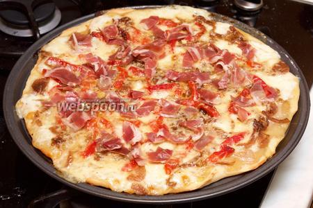 Вынуть пиццу и выложить сверху прошутто.