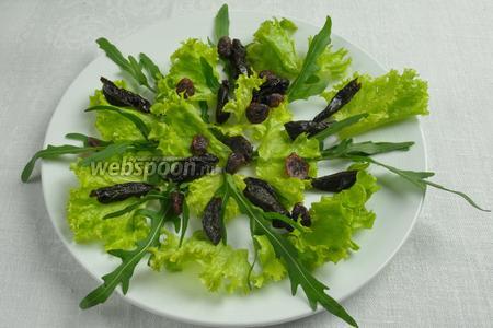 Собрать салат: на дно салатника выложить зелень, салат и сухофрукты.