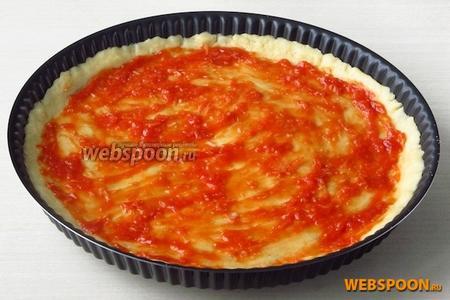 Приготовление пиццы. Лепёшку теста смазать томатно-чесночной смесью.