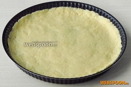 Готовое тесто раскатать в пласт толщиной 6–7 мм на 3 см больше диаметра формы для выпечки, и уложить в подготовленную форму. Края теста подвернуть, чтобы образовался небольшой бортик, который не позволит вытечь начинке. Края бортика прижать.