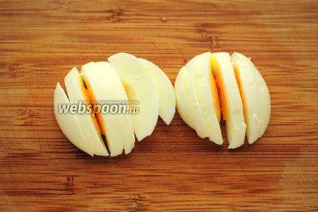 Сваренное вкрутую яйцо порезать пополам, а затем на ломтики.