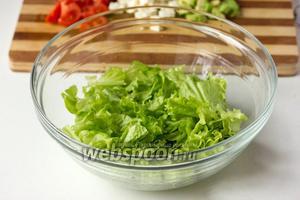 Листья салата моем под проточной водой, лишнюю воду аккуратно промакиваем бумажным полотенцем, нарываем салат в глубокую миску средними кусками.