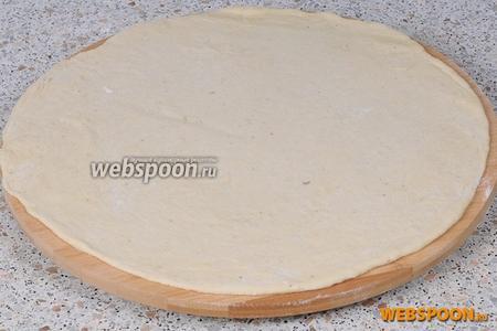 Обильно посыпаем поверхность доски мукой, после чего тонко раскатываем тесто, толщиной примерно 0,5 см, диаметр у меня около 30 см.