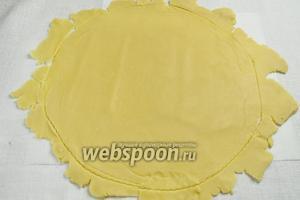Достать тесто, согреть его с помощью рук, слегка помешивая. На пергаментной бумаге раскатать тесто тонким слоем 3,5 мм. Разрежьте тесто по кругу на 2 см шире, чем форма для выпечки.