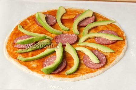 Выкладываем на тесто для пиццы по всей площади ломтики авокадо и колбасы.