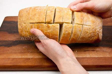 Чиабатту разрезать вдоль, а затем поперёк, не касаясь ножом основания хлеба.
