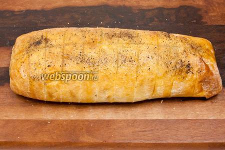 Полить оливковым маслом, заливая масло вовнутрь хлеба, поперчить и посолить.