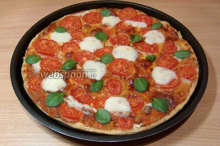 Выпекать пиццу 10-15 минут при температуре 220 °C. Так как Моцарелла быстро образует румяную корочку, а нам нужно сохранить белый цвет, за 3-5 минут до готовности необходимо добавить свежие кусочки Моцареллы и, как только она расплавится, тут же вынуть пиццу. Украсить листочками свежего базилика – и итальянский триколор готов. К сожалению, зелёного базилика я нигде не могла купить, поэтому использовала листочки салата корн.