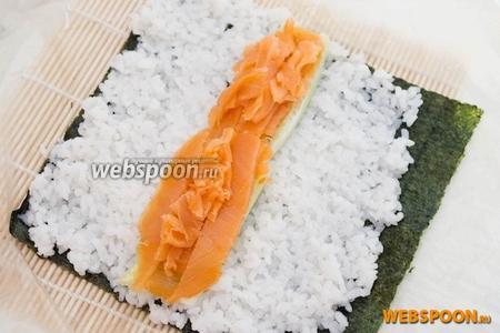 Оберните бамбуковый коврик в целофановый пакет. Выложите лист нори и сверху выложите тонкий слой риса, оставляя 1-2 см с одного краю. Выложите огурец и лосось.