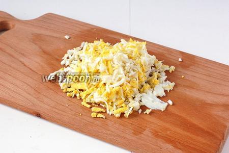 Яйца отварить вкрутую, очистить и натереть на мелкой тёрке.