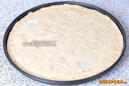 Вот мы и добрались до теста, его нужно растянуть руками по форме для выпекания пиццы, делать это нужно аккуратно, посыпая мукой и приминая ладонями, так как тесто у нас довольно тонкое.
