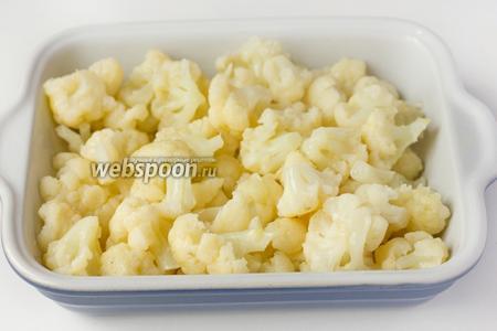 С отваренной цветной капусты сливаем воду, выкладываем капусту в форму для запекания, заливаем сырыми яйцами и тщательно перемешиваем.