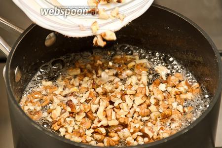 Далее высыпаем в сахарный сироп орехи, муку и добавляем 1 щепотку лимонной кислоты. Варим на медленном огне 15 минут, постоянно помешивая. Также, на этой стадии нужно проследить, чтобы не осталось комочков муки. Если таковые имеются, то их можно растереть ложкой о стенки кастрюли.