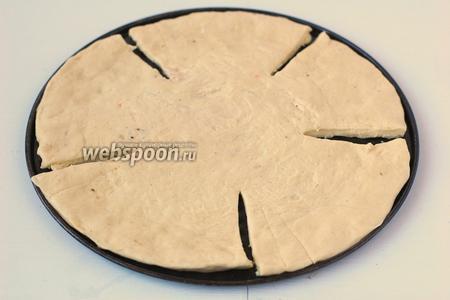 Тесто равномерно распределить руками по форме диаметром 23 см. Разрезать тесто на 5 сегментов не дорезая до центра.