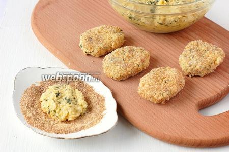Формировать небольшие лепёшки, обкатывая их в сухарях.