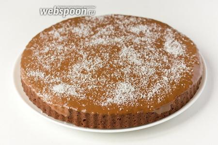 Сразу же поливаем шоколадной глазурью остывший шоколадно-кокосовый кекс, посыпаем кокосовой стружкой. Подаём к столу, когда глазурь остынет и/или застынет. Подаём к нему молоко.
