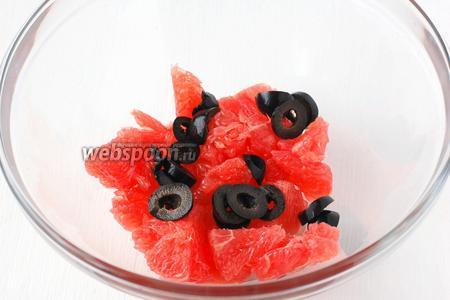 В салатник с порезанным грейпфрутом добавит порезанные колечками маслины.