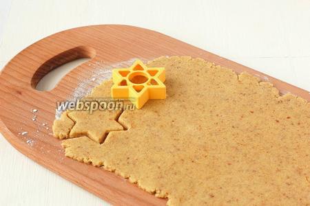 Раскатать тесто на подпыленной мукой доске толщиной 0,8 см. Вырезать формочкой печенье.