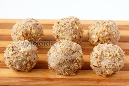 Сформировать из паштета шарики величиной с грецкий орех, обвалять в оставшихся измельчённых грецких орехах.